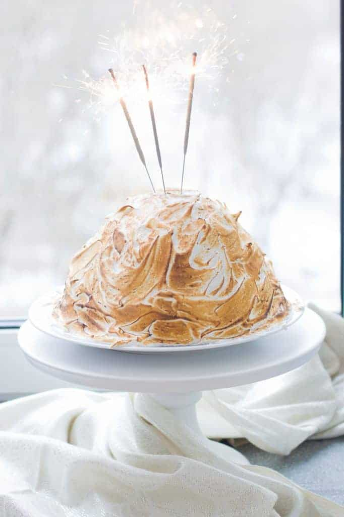 Photo of a Baked Alaska dessert on a white cake stand with sparklers.