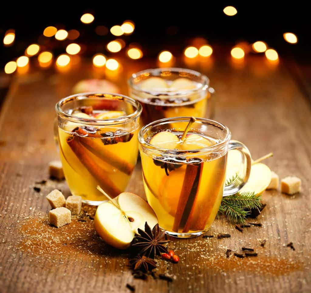 Hot spiked apple cider in glass mugs in front of twinkly lights